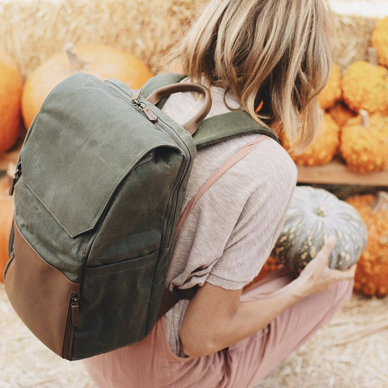 A blonde woman wearing an olive green backpack squatting down to pick up a green pumpkin at a pumpkin patch